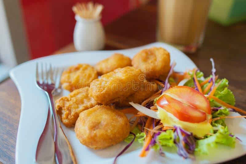 Το κοτόπουλο τηγάνισε τα ψήγματα με το λαχανικό σαλάτας και το γάλα καφέ στον ξύλινο πίνακα μέσα στο φως του παραθύρου στοκ εικόνες