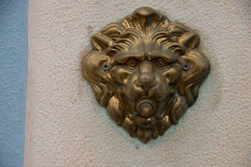Το κουδούνι πορτών με το κεφάλι ενός λιονταριού, το γυαλισμένο κουμπί ορείχαλκου στοκ φωτογραφία με δικαίωμα ελεύθερης χρήσης