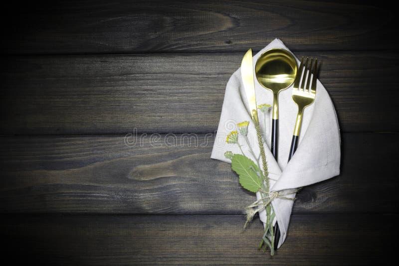 Το κουτάλι, το δίκρανο, το μαχαίρι και το καλοκαίρι ανθίζουν σε έναν ξύλινο εκλεκτής ποιότητας πίνακα στοκ εικόνα με δικαίωμα ελεύθερης χρήσης