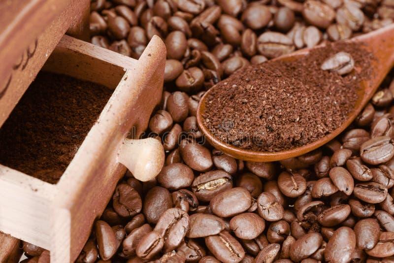 Το κουτάλι μπαμπού με τον επίγειο καφέ, τα φασόλια καφέ και το μύλο καφ στοκ φωτογραφίες