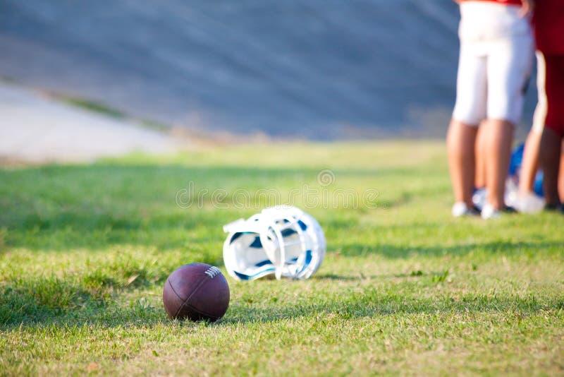 Το κράνος και η σφαίρα ποδοσφαίρου στο έδαφος κλείνουν το περιθώριο στοκ εικόνες