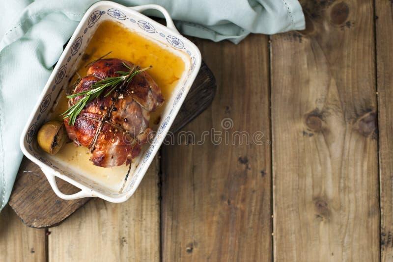 Το κρέας έδεσε με το σχοινί, που ψήθηκε σε μια κρούστα σε ένα φύλλο ψησίματος με τον ασβέστη και το δεντρολίβανο, σε έναν ξύλινου στοκ εικόνα με δικαίωμα ελεύθερης χρήσης
