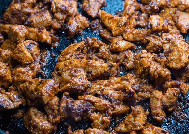 Το κρέας στο μαρινάρισμα τηγάνισε σε ένα τηγανίζοντας τηγάνι, πολλά clos κομματιών κοτόπουλου στοκ εικόνες