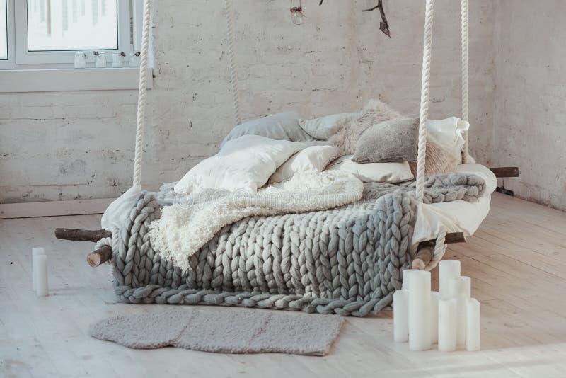 Το κρεβάτι που αναστέλλεται από το ανώτατο όριο Το γκρίζο μεγάλο άνετο κάλυμμα πλέκει Σκανδιναβικό ύφος, γκρίζο καρό, κεριά στοκ εικόνες