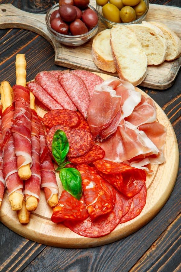 Το κρύο κάπνισε το πιάτο κρέατος με τις μπριζόλες χοιρινού κρέατος, τα ραβδιά prosciutto, σαλαμιού και ψωμιού στοκ εικόνα με δικαίωμα ελεύθερης χρήσης