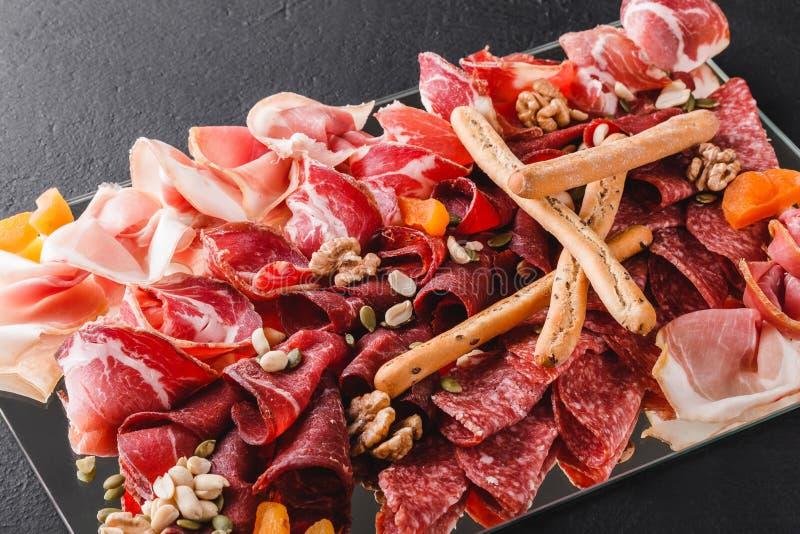 Το κρύο κρέας πιατελών Antipasto με τα ραβδιά ψωμιού grissini, prosciutto, τεμαχίζει το ζαμπόν, βόειο κρέας jerky, σαλάμι στοκ εικόνα