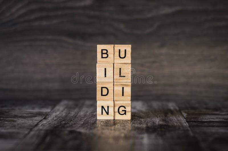 Το κτήριο λέξης φιαγμένο από φωτεινούς ξύλινους κύβους με τα μαύρα γράμματα ο στοκ φωτογραφία με δικαίωμα ελεύθερης χρήσης