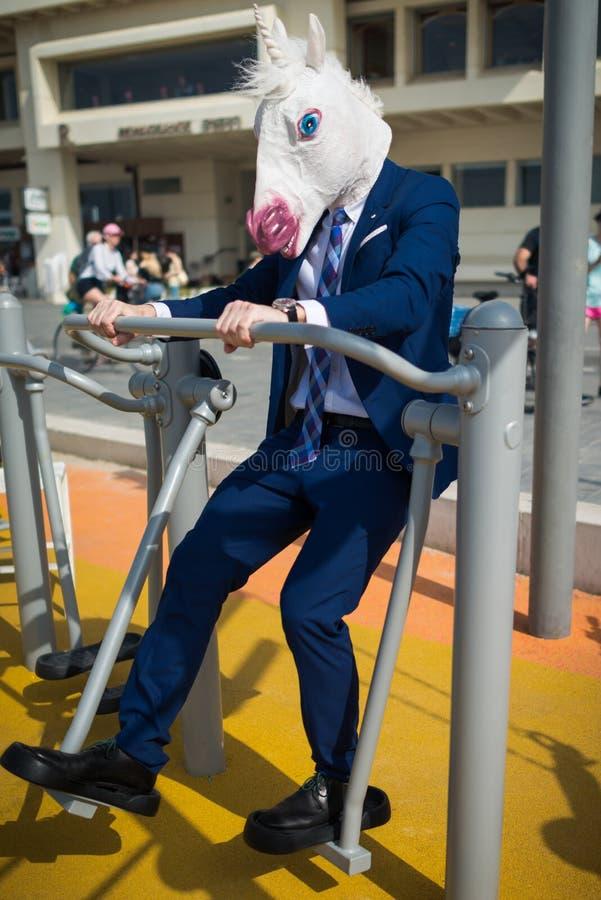 Το κωμικό άτομο στο κομψό κοστούμι και την αστεία μάσκα κάνει τις αθλητικές ασκήσεις στοκ φωτογραφίες με δικαίωμα ελεύθερης χρήσης