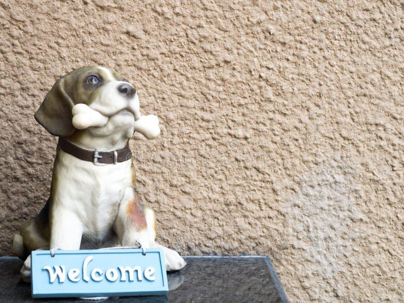 Το κόκκαλο δαγκωμάτων σκυλιών γλυπτών και έχει το μπλε ευπρόσδεκτο σημάδι στο μέτωπο στοκ φωτογραφία