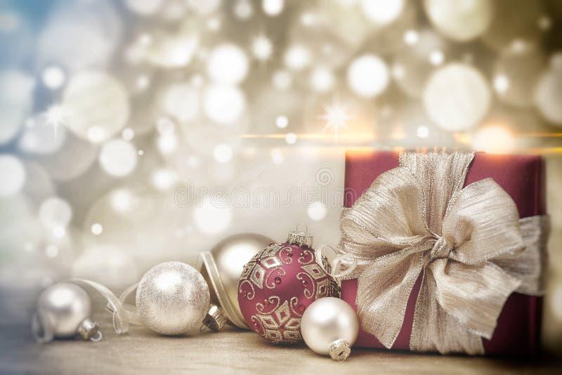 Το κόκκινα κιβώτιο και τα μπιχλιμπίδια δώρων Χριστουγέννων στο υπόβαθρο τα χρυσά φω'τα στοκ εικόνες