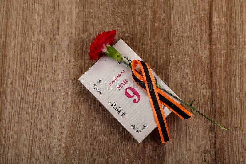 Το κόκκινο γαρίφαλο με την κορδέλλα του ST Georges είναι το σύμβολο της ημέρας νίκης στοκ φωτογραφία με δικαίωμα ελεύθερης χρήσης