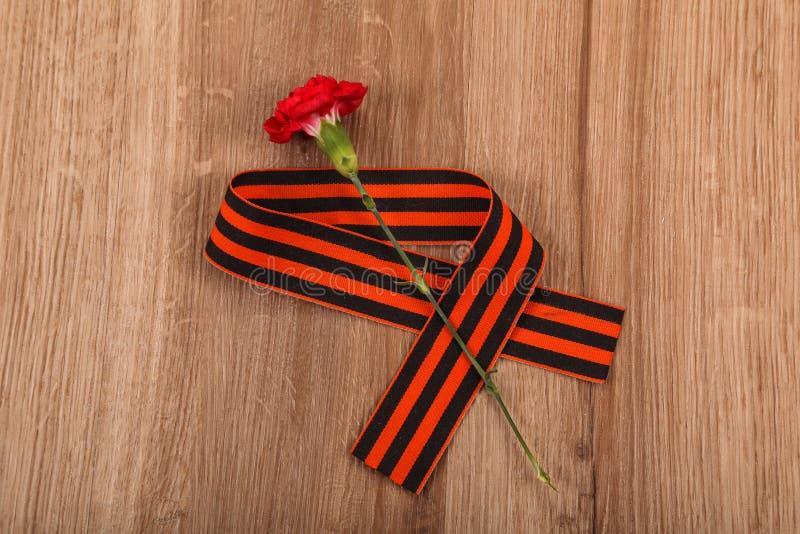 Το κόκκινο γαρίφαλο με την κορδέλλα του ST Georges είναι το σύμβολο της ημέρας νίκης στοκ φωτογραφία