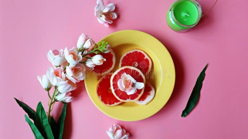 Το κόκκινο γκρέιπφρουτ τεμαχίζει τα ζωηρόχρωμα πιάτα καλύπτει το κίτρινο φλυτζάνι στο ρόδινο κόκκινο απεικόνισης υποβάθρου εμβλημ στοκ φωτογραφία