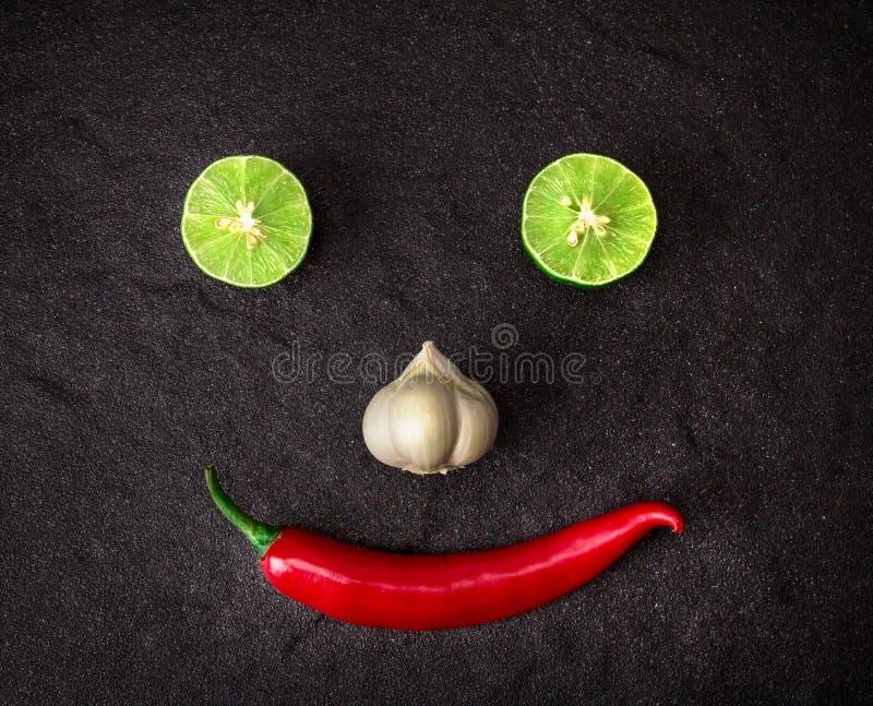 Το κόκκινο λεμόνι τσίλι, σκόρδου και ασβέστη τακτοποιεί ως πρόσωπο χαμόγελου στο bla στοκ εικόνες