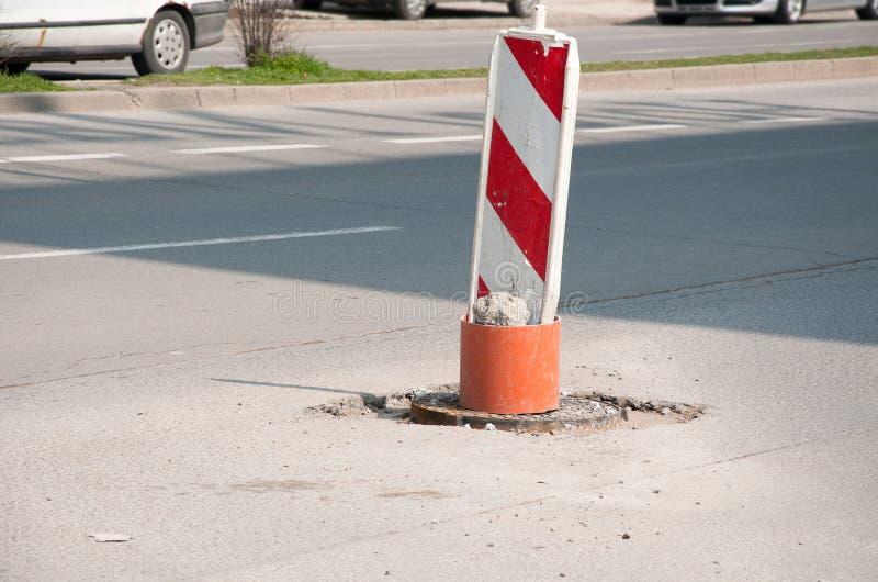 Το κόκκινο και άσπρο σημάδι προσοχής οδοφραγμάτων αναδημιουργίας ή κατασκευής οδών καλύπτει την ανοικτή τρύπα της καταπακτής στο  στοκ φωτογραφία