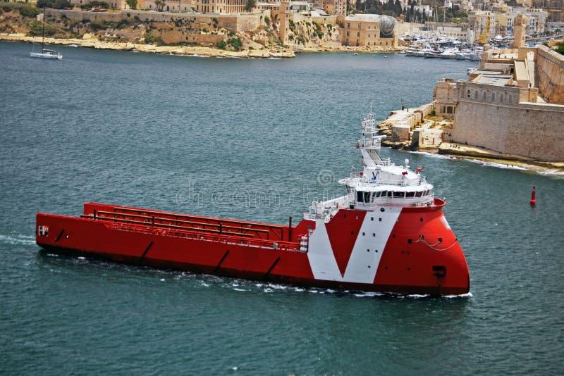Το κόκκινο και άσπρο σκάφος πλέει στο λιμάνι σε Vallenta Μάλτα στοκ εικόνες με δικαίωμα ελεύθερης χρήσης