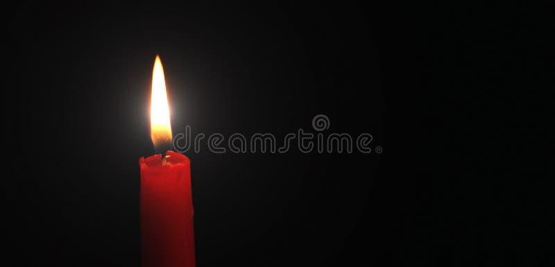 Το κόκκινο κερί άναψε λαμπρά το μαύρο υπόβαθρο στοκ εικόνες