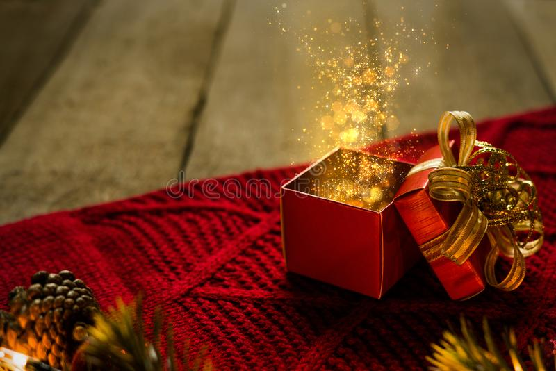 Το κόκκινο κιβώτιο δώρων Χριστουγέννων στο κόκκινο scraf με τα χρυσά μόρια ανάβει μαγικό στο ξύλινο γραφείο στοκ φωτογραφίες
