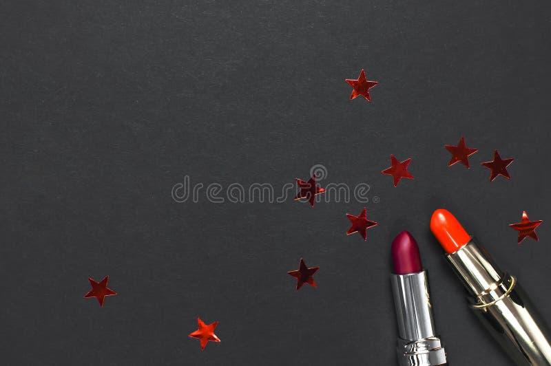 Το κόκκινο κραγιόν, ολογραφικό κομφετί στο μαύρο επίπεδο άποψης υποβάθρου τοπ βάζει με το διάστημα αντιγράφων Επαγγελματικές Make στοκ φωτογραφία