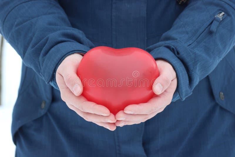 Το κόκκινο μπαλόνι με μορφή ενός ατόμου καρδιών κρατά στα χέρια του δώρο μια παγωμένη ημέρα στις 14 Φεβρουαρίου - ημέρα του βαλεν στοκ φωτογραφία με δικαίωμα ελεύθερης χρήσης