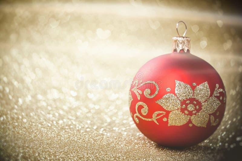 Το κόκκινο μπιχλιμπίδι Χριστουγέννων στο υπόβαθρο τα χρυσά φω'τα στοκ φωτογραφία με δικαίωμα ελεύθερης χρήσης