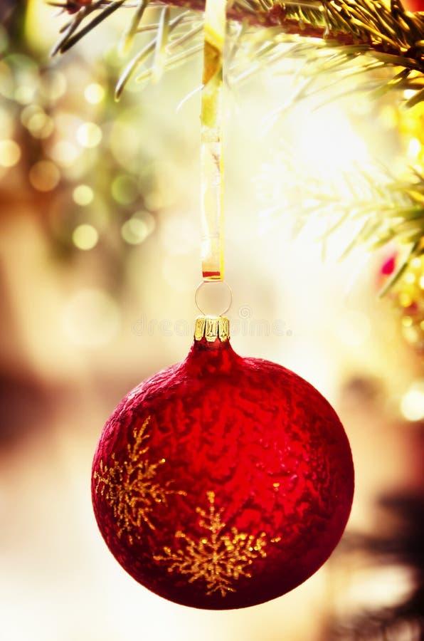Το κόκκινο μπιχλιμπίδι Χριστουγέννων στο χριστουγεννιάτικο δέντρο λάμπει επάνω ελαφρύ υπόβαθρο, κλείνει επάνω στοκ εικόνες