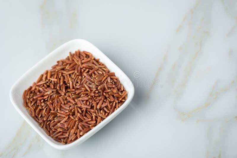 Το κόκκινο ξεφλουδισμένο ακατέργαστο ρύζι της Jasmine στο κύπελλο πορσελάνης στο μαρμάρινο υπόβαθρο και είναι μια ειδικότητα από  στοκ εικόνα με δικαίωμα ελεύθερης χρήσης
