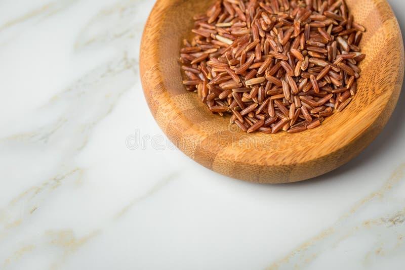 Το κόκκινο ξεφλουδισμένο ακατέργαστο ρύζι της Jasmine στο ξύλινο κύπελλο μπαμπού στο μαρμάρινο υπόβαθρο και είναι μια ειδικότητα  στοκ εικόνες