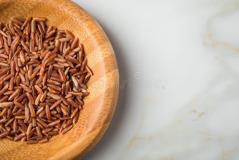 Το κόκκινο ξεφλουδισμένο ακατέργαστο ρύζι της Jasmine στο ξύλινο κύπελλο μπαμπού στο μαρμάρινο υπόβαθρο και είναι μια ειδικότητα  στοκ φωτογραφίες