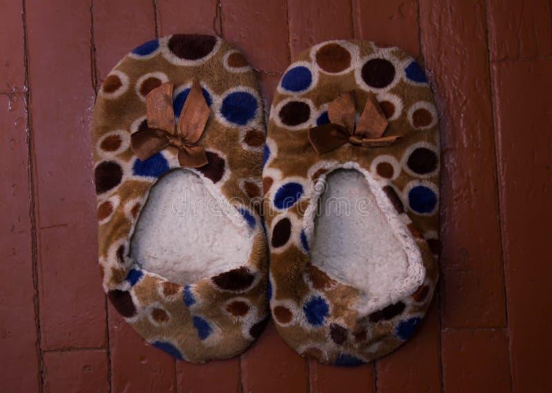 Το κόκκινο παπούτσι παντοφλών στην μπλε σύσταση μαλακότητας χαλιών ταπήτων διακόσμησε το εσωτερικό σπίτι πατωμάτων στοκ εικόνες