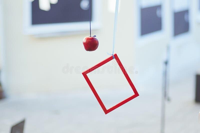 Το κόκκινο πλαίσιο ζυγίζει, κρεμασμένο κόκκινο μήλο Τέχνη οδών στοκ φωτογραφία