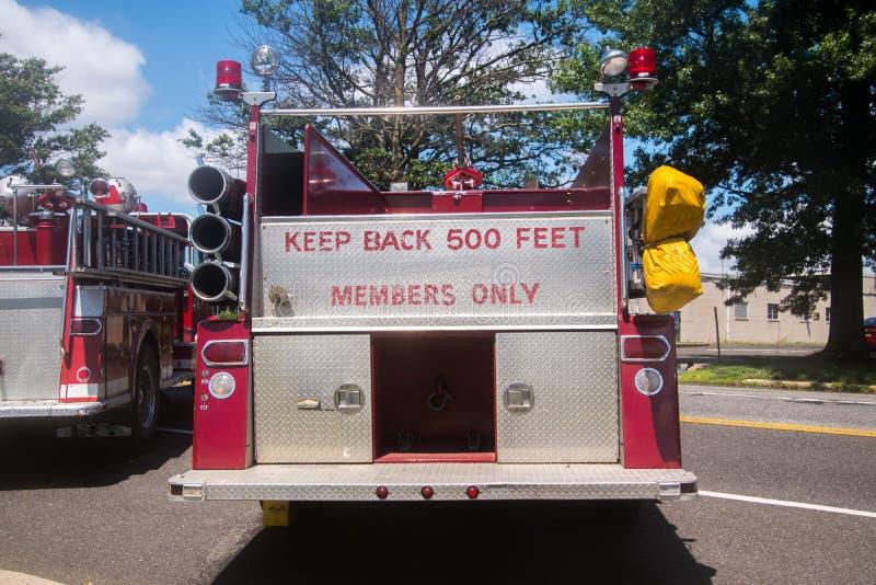 Το κόκκινο πυροσβεστικό όχημα με τις λέξεις κρατά πίσω 500 πόδια και μέλη ασθμαμένα μόνο στο κόκκινο στο χρώμιο στην πλάτη στοκ φωτογραφίες με δικαίωμα ελεύθερης χρήσης