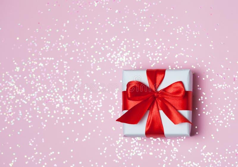 Το κόκκινο τόξο κιβωτίων 6ος δώρων και ακτινοβολεί σπινθηρίσματα στο ρόδινο υπόβαθρο Έννοια ημέρας βαλεντίνων ` s του ST στοκ φωτογραφία με δικαίωμα ελεύθερης χρήσης
