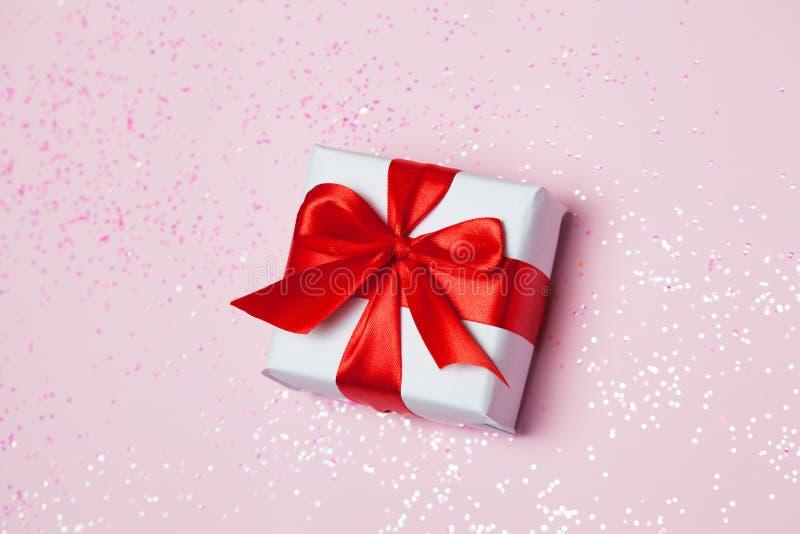 Το κόκκινο τόξο κιβωτίων 6ος δώρων και ακτινοβολεί σπινθηρίσματα στο ρόδινο υπόβαθρο Έννοια ημέρας βαλεντίνων ` s του ST στοκ εικόνες