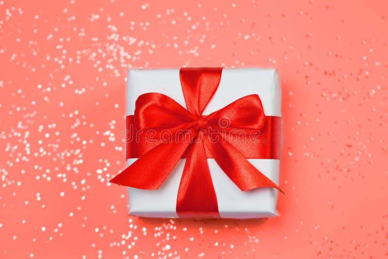 Το κόκκινο τόξο κιβωτίων 6ος δώρων και ακτινοβολεί σπινθηρίσματα στο υπόβαθρο κοραλλιών διαβίωσης Έννοια ημέρας βαλεντίνων ` s στοκ εικόνα με δικαίωμα ελεύθερης χρήσης