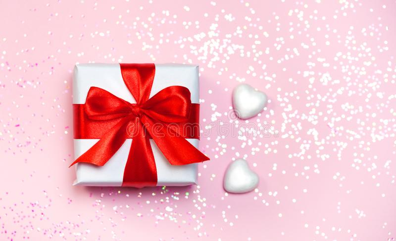Το κόκκινο τόξο κιβωτίων 6ος δώρων και ακτινοβολεί σπινθηρίσματα στο ρόδινο υπόβαθρο Έννοια ημέρας βαλεντίνων ` s του ST στοκ εικόνα