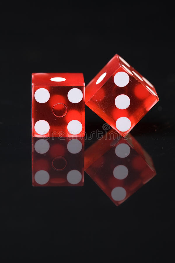 Το κόκκινο χωρίζει σε τετράγωνα με τους άσπρους σπόρους στον αντανακλαστικό μαύρο πίνακα στοκ φωτογραφία