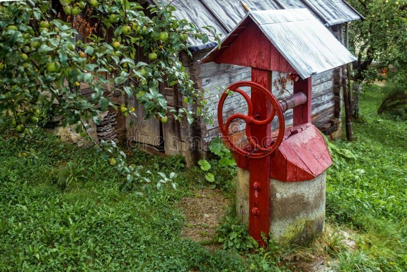 Το κόκκινο χωριό καλά κοντά σε ένα ξύλινο εξοχικό σπίτι στοκ εικόνες