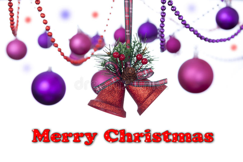 Το κόκκινο δύο ακτινοβολεί κουδούνια που κρεμούν σε μια κορδέλλα ταρτάν με τα μπιχλιμπίδια Χριστουγέννων με ένα χιονώδες σημάδι Χ στοκ φωτογραφία με δικαίωμα ελεύθερης χρήσης