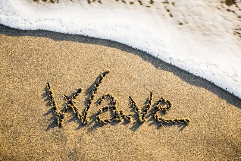 Το κύμα που έρχεται γλυπτός στην άμμο στοκ εικόνες