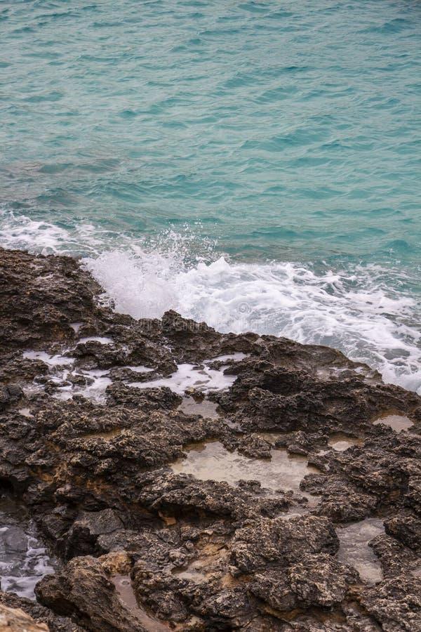 Το κύμα συναντά τη δύσκολη ακτή ασβεστόλιθων στον μπλε κόλπο λιμνοθαλασσών, νησί Comino, Μάλτα στοκ εικόνες με δικαίωμα ελεύθερης χρήσης