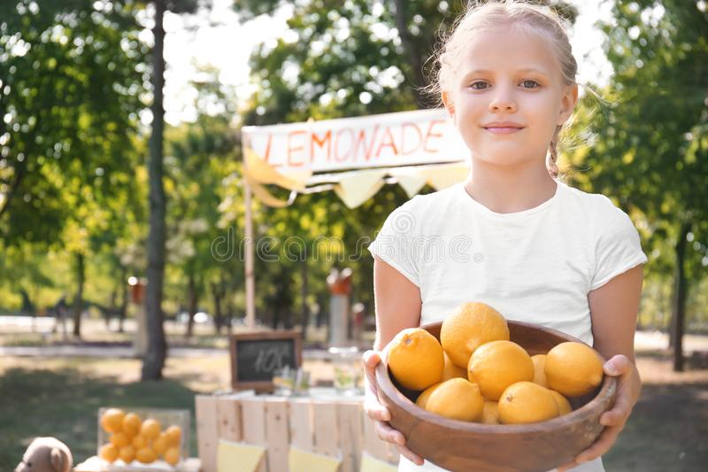 Το κύπελλο εκμετάλλευσης μικρών κοριτσιών με τα ώριμα λεμόνια στέκεται πλησίον στο πάρκο στοκ εικόνες με δικαίωμα ελεύθερης χρήσης