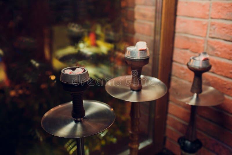 Το κύπελλο shisha αργίλου με την τέχνη ο καπνός και το κόκκινο - καυτή σπείρα καρύδων με το μαύρο υπόβαθρο καπνού hookah που απομ στοκ φωτογραφία