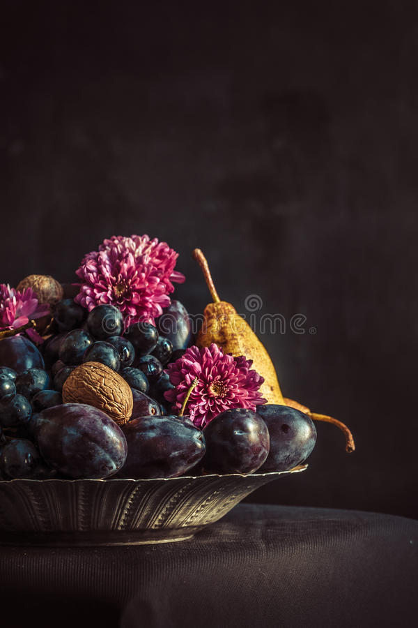 Το κύπελλο φρούτων με τα σταφύλια και τα δαμάσκηνα ενάντια σε έναν σκοτεινό τοίχο στοκ εικόνες