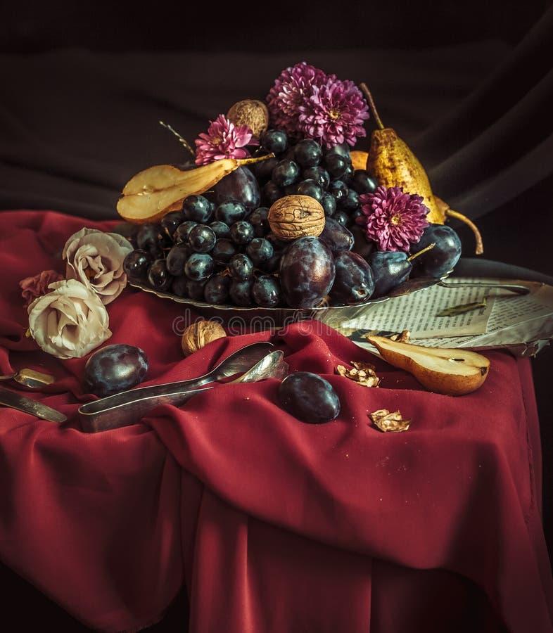 Το κύπελλο φρούτων με τα σταφύλια και τα δαμάσκηνα ενάντια σε ένα καφέ τραπεζομάντιλο στοκ φωτογραφία με δικαίωμα ελεύθερης χρήσης