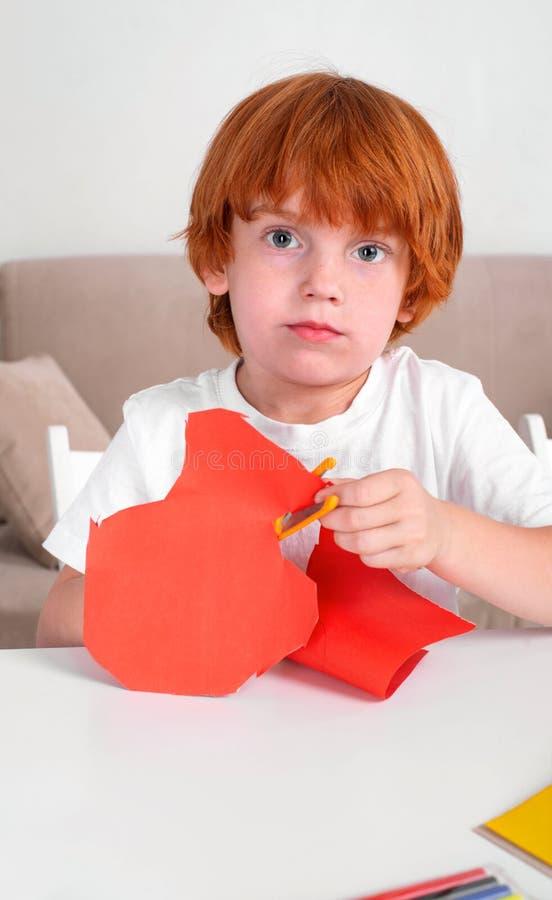 Το λίγο κοκκινομάλλες αγόρι κάθεται στον πίνακα και αποκόπτει του χρωματισμένου εγγράφου με το ψαλίδι Μαθαίνει και αναπτύσσεται στοκ φωτογραφίες με δικαίωμα ελεύθερης χρήσης