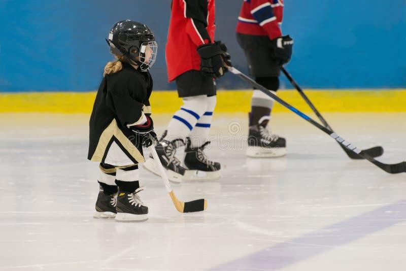 Το λίγο χαριτωμένο κορίτσι χόκεϋ είναι στον πάγο που φορά στον πλήρη εξοπλισμό: κράνος χόκεϋ, γάντια, ραβδί, σαλάχια Αριθμοί του  στοκ εικόνα με δικαίωμα ελεύθερης χρήσης