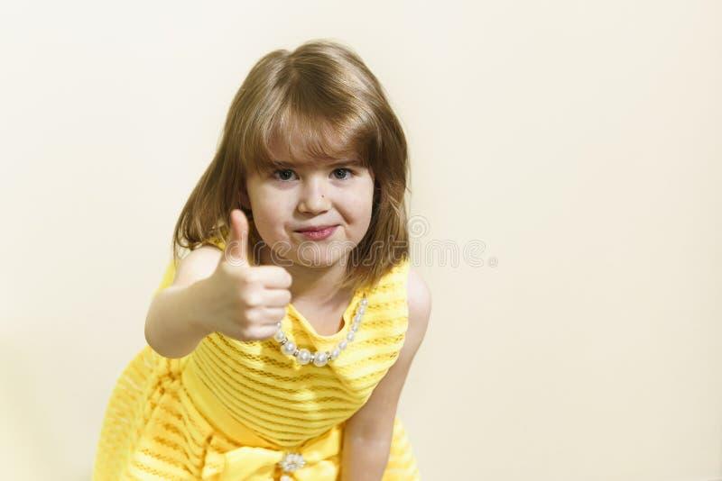 Το λίγο όμορφο κορίτσι σε ένα κίτρινο φόρεμα παρουσιάζει αντίχειρά της Αυτός είναι εντάξει στοκ εικόνες με δικαίωμα ελεύθερης χρήσης