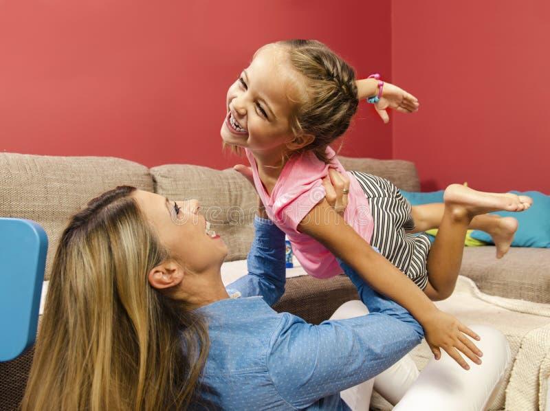 Το λατρευτό ευτυχές πέταγμα μικρών κοριτσιών ρίχνει τον αέρα στα όπλα μητέρων της στοκ φωτογραφία με δικαίωμα ελεύθερης χρήσης