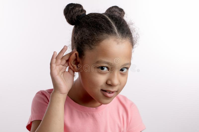 Το λατρευτό συμπαθητικό μαύρος-μαλλιαρό κορίτσι έλεγξε την ακρόασή της στοκ φωτογραφίες